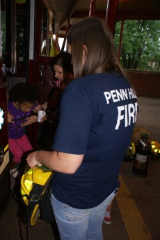 Firefighter Nicole helping kids out of engine